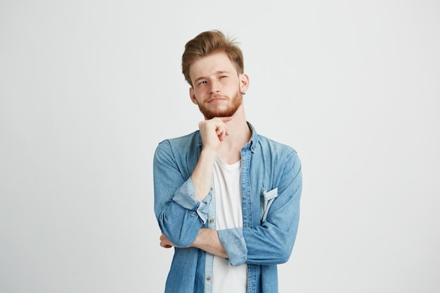 Portrait of dreamy young handsome guy thinking dreaming with hand on chin. Free Photo