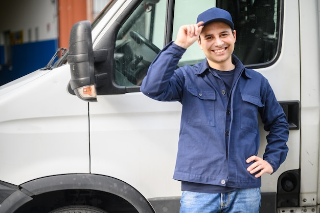 Portrait of a driver standing enar his van and smiling Premium Photo