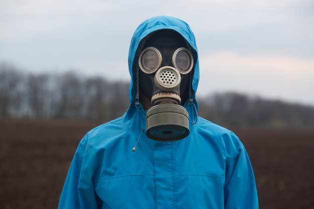 Portrait of ecologist working outdoors, wearing gas mask and uniform, scientist explores surroundings, scientist works in open air Free Photo