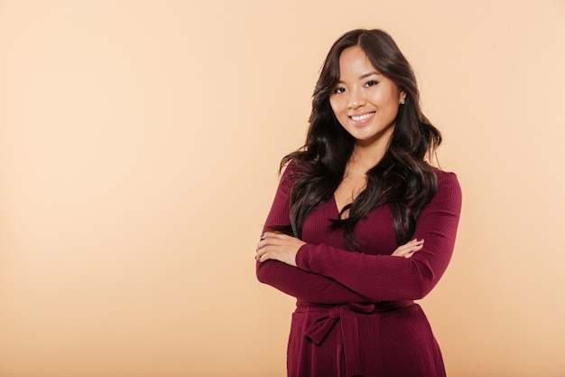 Portrait of elegant asian female in pretty maroon dress posing on camera with arms folded isolated over peach background Free Photo