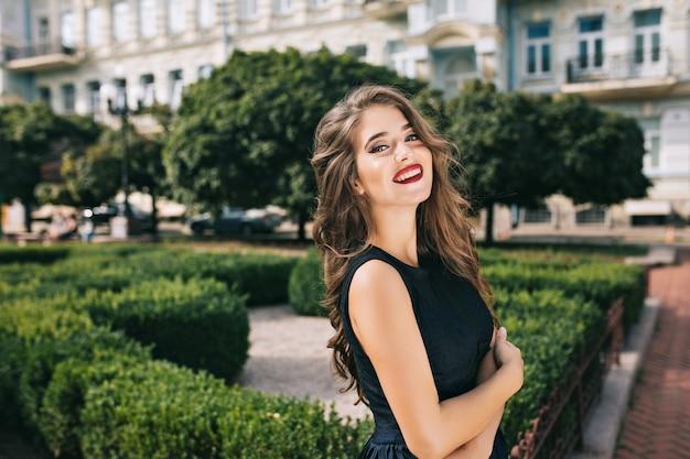 Ritratto di ragazza elegante con capelli lunghi e labbra vinose in cortile. indossa un abito nero e sorride. Foto Gratuite