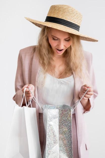 Ritratto della donna elegante che controlla gli acquisti Foto Gratuite