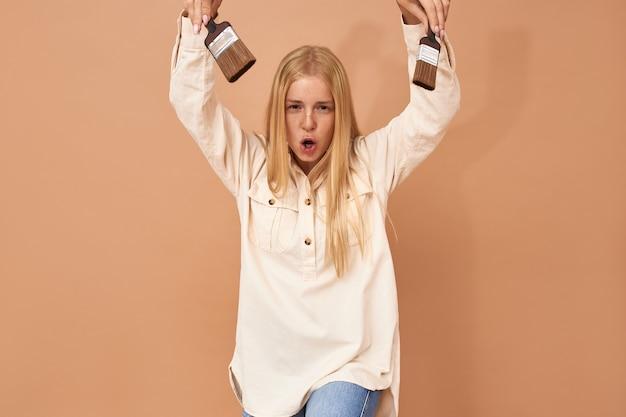 Ritratto di giovane femmina allegra emotiva divertendosi al chiuso mentre dipinge le pareti nel suo appartamento, tenendo in mano due pennelli, facendo una smorfia divertente, aprendo ampiamente la bocca Foto Gratuite