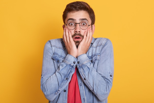 Portrait of emotional shocked scared guy opening eyes and mouth widely, putting hands to face, having impressed facial expression Free Photo