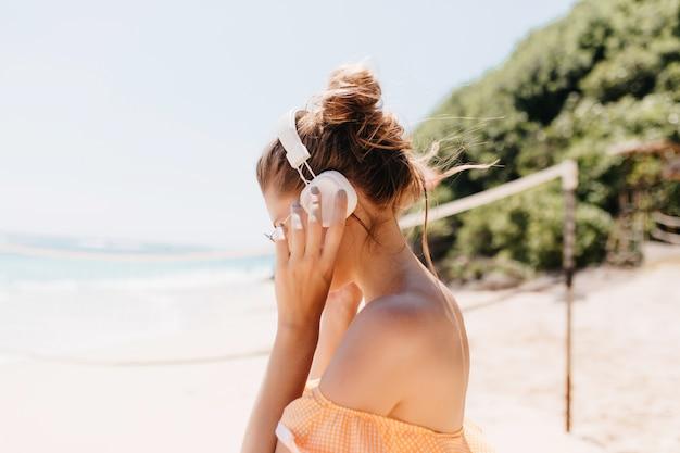 Ritratto di incantevole signora con i capelli scuri in posa sulla costa dell'oceano. incredibile donna abbronzata agghiacciante in estate in località esotica. Foto Gratuite
