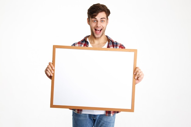 Portrait of an excited cheerful guy holding blank board Free Photo
