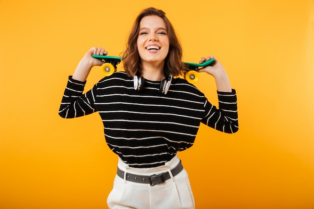Portrait of an excited girl holding skateboard on her shoulders Free Photo