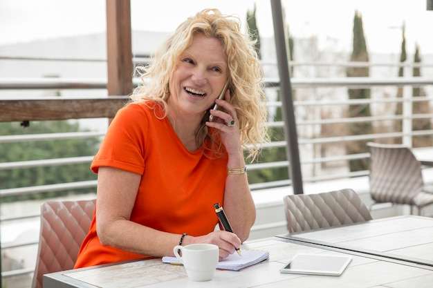 Portrait of excited mature businesswoman talking on mobile phone Free Photo