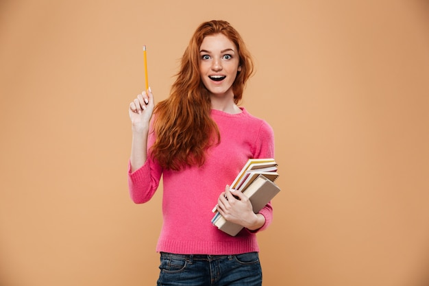 Portrait of an excited pretty redhead girl holding books and having an idea Free Photo