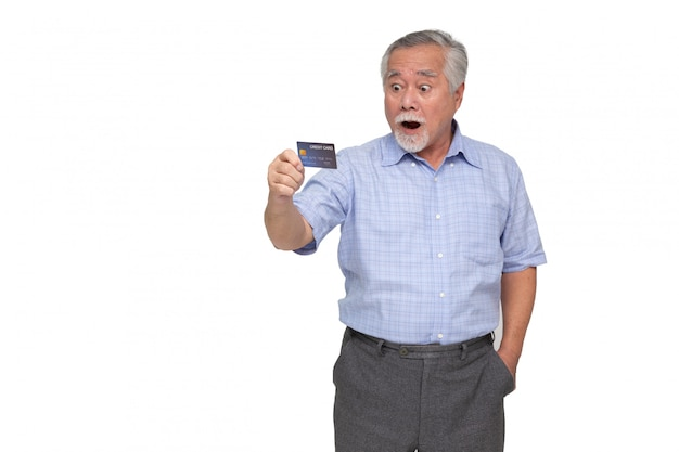 Portrait of excited screaming senior asian man standing and holding credit card isolated, wow and surprised concept Premium Photo
