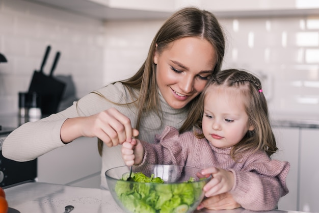 Portrait of excited woman eating cooked healthy food salad with her little daughter Free Photo