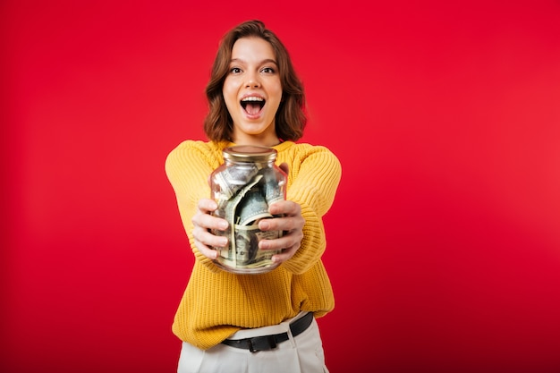Portrait of an excited woman showing jar Free Photo