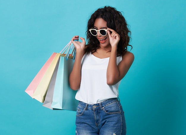 Portrait of an excited young black woman hand holding shopping bag and sunglasses Premium Photo