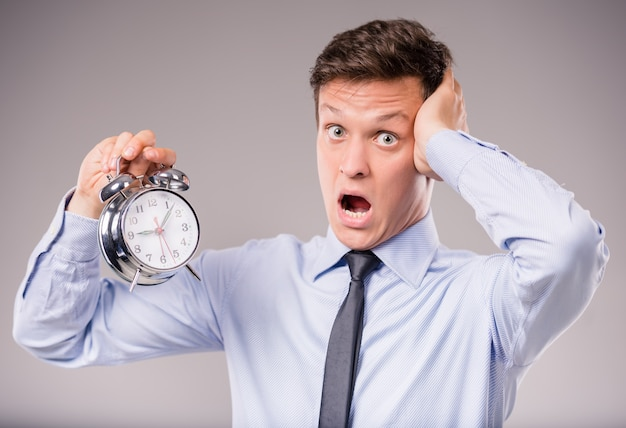 Portrait of excited young businessman holding a clock. Premium Photo