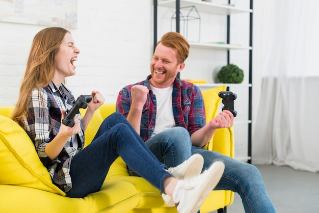 Portrait of excited young couple enjoying playing the video game at home Free Photo
