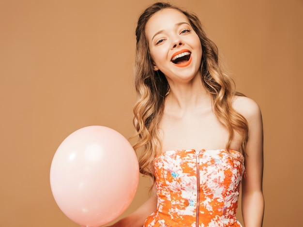 Portrait of excited young girl posing in trendy summer colorful dress. smiling woman with pink balloon posing. model ready for party Free Photo