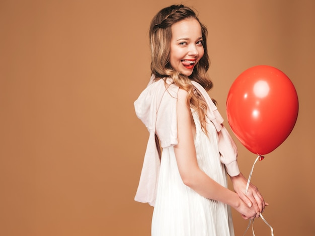Portrait of excited young girl posing in trendy summer white dress. smiling woman with red balloon posing. model ready for party, showing her tongue Free Photo