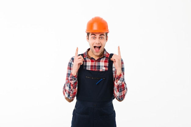 Portrait of an excited young male builder pointing Free Photo