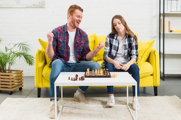Portrait of a excited young man sitting with her sad girlfriend playing chess game Free Photo