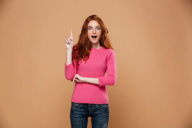 Portrait of an excited young redhead girl pointing up with fingers Free Photo