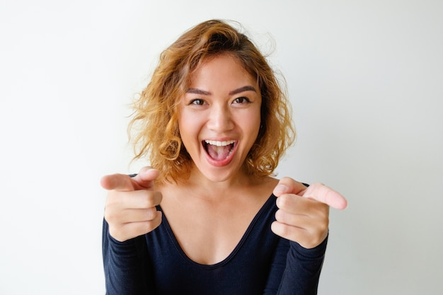 Portrait of excited young woman pointing at camera Free Photo