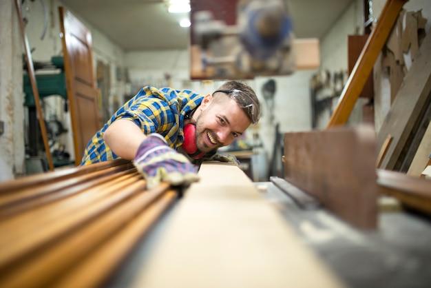 Ritratto di falegname esperto lavoratore taglio tavola di legno sulla macchina nel suo laboratorio di falegnameria Foto Gratuite