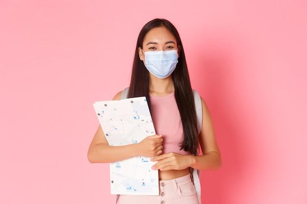 Портрет выразительной молодой женщины, держащей карту и носящей маску Бесплатные Фотографии