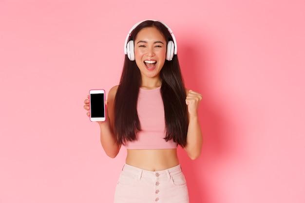 Портрет выразительной молодой женщины с наушниками, слушающей музыку Бесплатные Фотографии