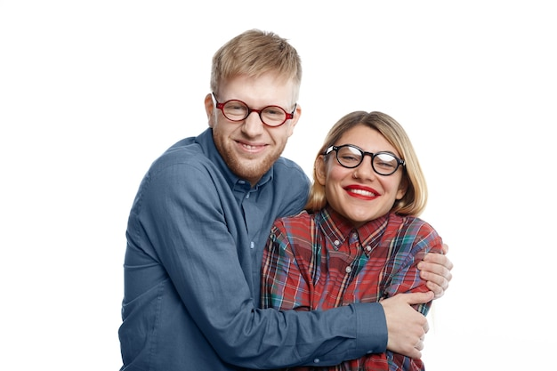 Portrait of extraordinary comic young caucasian couple in eccentric clothes and eyewear having fun: geeky man with stubble hugging tight his happy attractive girlfriend with red lips and fair hair Free Photo