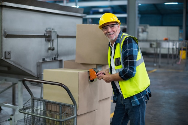 Portrait of factory worker loading cardboard boxes Premium Photo