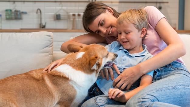 Ritratto di famiglia che gioca con il simpatico cane Foto Gratuite