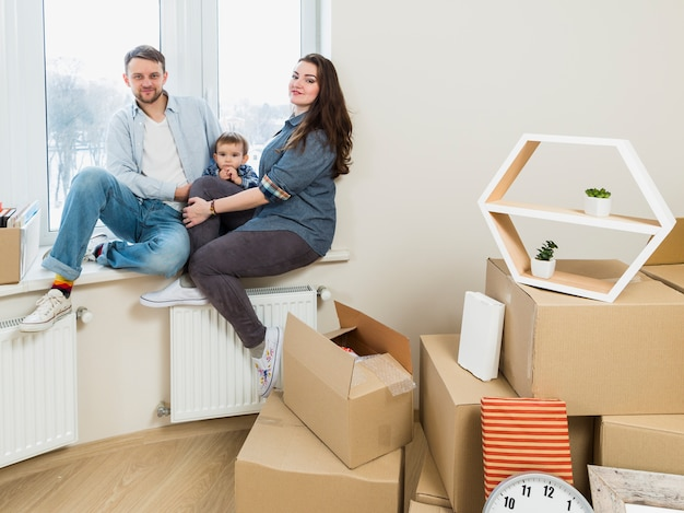 Portrait of a family with moving cardboard boxes in their new home Free Photo