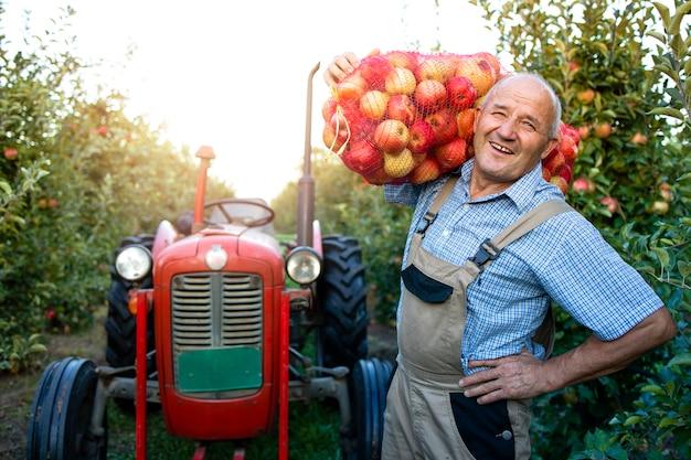 Ritratto del lavoratore agricolo che tiene il sacco pieno di frutta mela Foto Gratuite