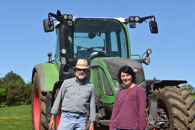 Portrait of a farmer couple and tractor on the field Premium Photo