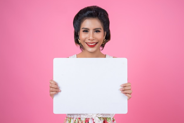 Portrait of fashion woman displaying white banner Free Photo
