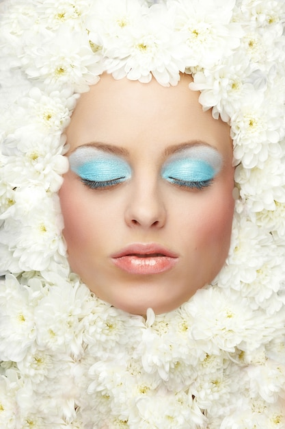 Portrait of fashion woman model with bright makeup lies in flowers Premium Photo