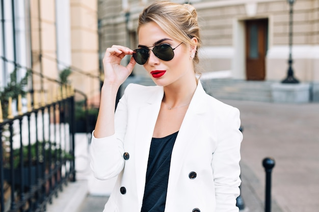 Portrait fashion woman in sunglasses with red lips on street. she is looking to camera. Free Photo