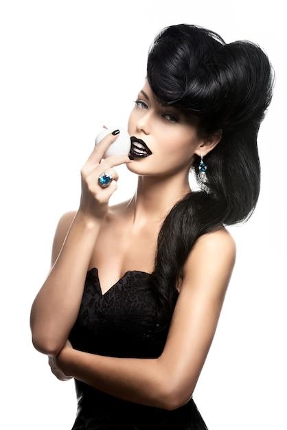 Ritratto di donna moda con acconciatura moderna e labbra in colore nero con mela bianca Foto Gratuite