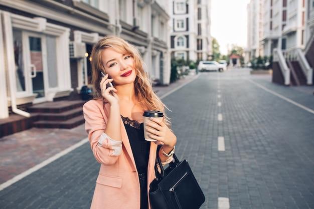 通りのサンゴジャケットを歩いて長い髪の肖像画のファッショナブルなブロンドの女性。彼女は電話で話している、カップを保持しています 無料写真