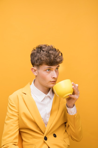 Portrait of fashionable boy drinking from a cup Free Photo