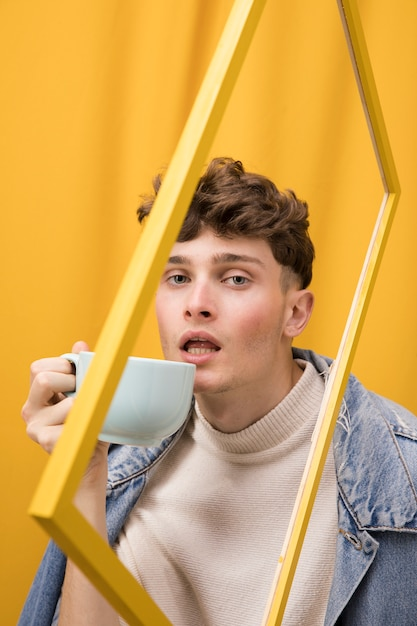 Portrait of fashionable boy drinking within a frame Free Photo