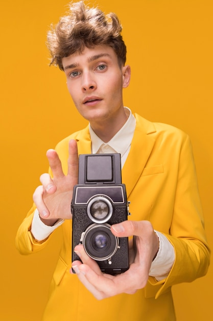 Portrait of fashionable boy filming with a camcorder Free Photo