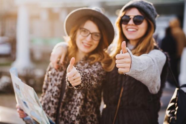 Портрет модных улыбающихся женщин, выражающих яркие эмоции в солнечный день в городе. счастливых путешествий вместе, прекрасных моментов веселых рекламистов, стильного образа, наслаждения отдыхом, счастья. Бесплатные Фотографии