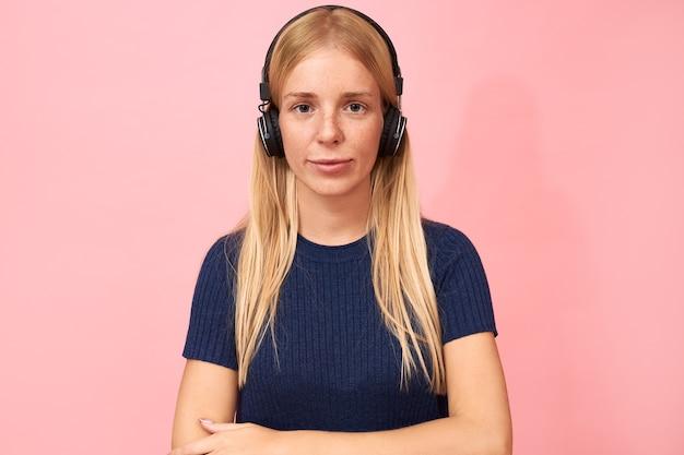 Ritratto di ragazza studentessa alla moda con anello al naso in posa sul rosa in cuffie wireless, ascoltando lezioni online, audiolibri o podcast Foto Gratuite