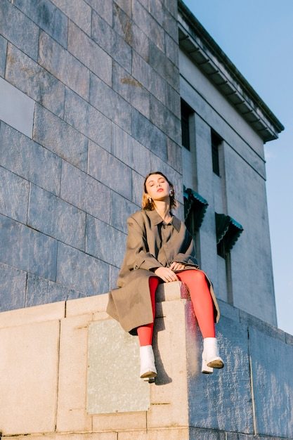 Portrait of a fashionable young woman sitting over the wall Free Photo