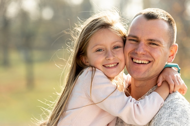 Portrait of father and daughter looking at photographer Free Photo