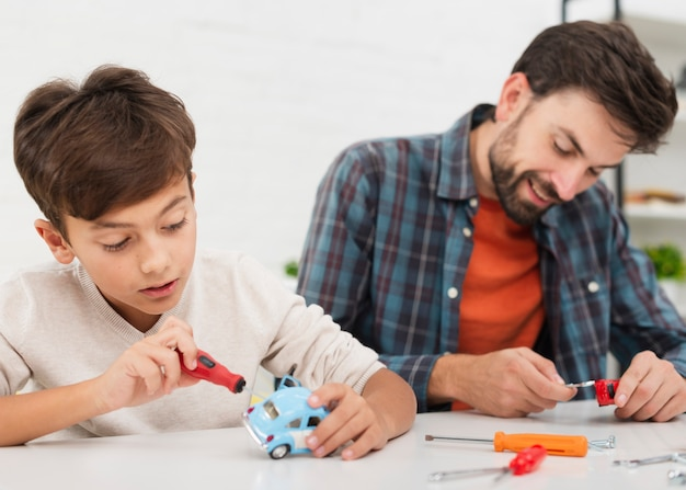 Portrait of father and son fixing toy cars Free Photo