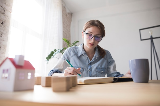 Portrait of a female architect writing on book at workplace Free Photo