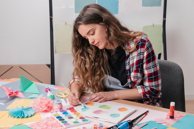 Portrait of female artist painting on white paper Free Photo
