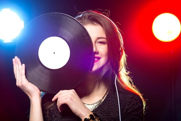Portrait of the female dj with vinyl record. Premium Photo
